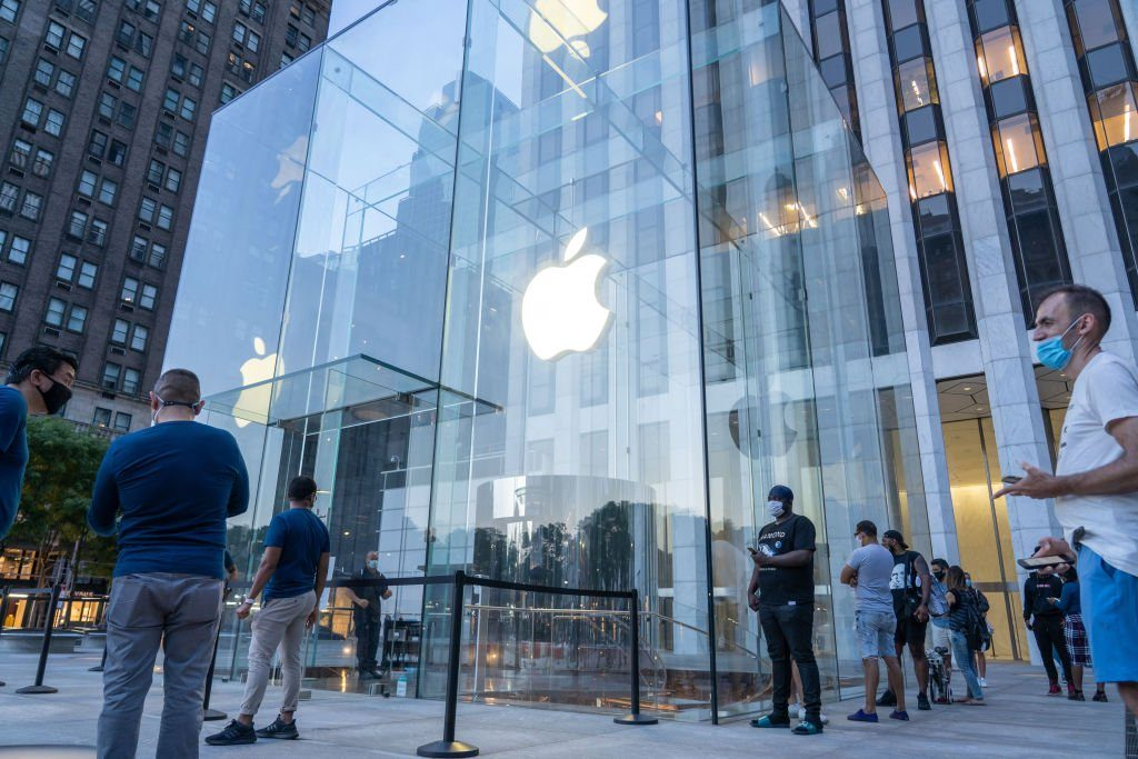 People stand in a socially distanced line outside the Apple...