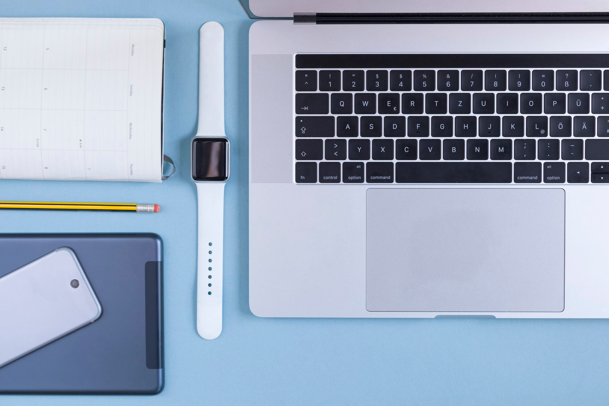 Various electronic devices, personal organizer and a pencil on blue ground