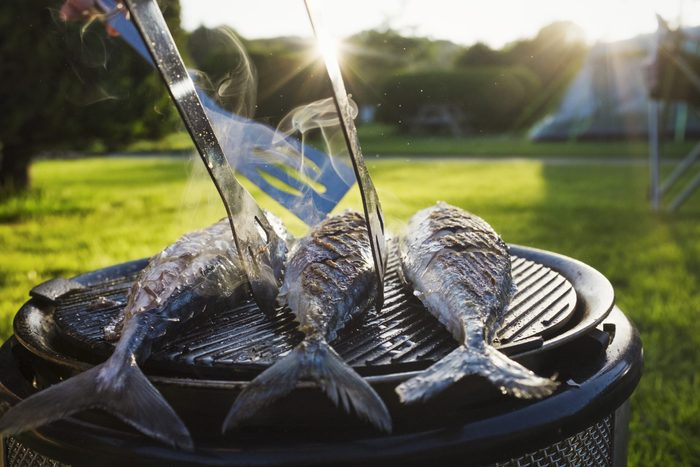 A small barbeque with three fresh mackerel fish on the grill, and a person using tongs to turn the fish.