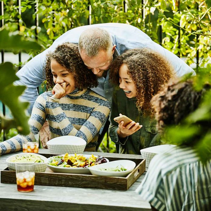 Father and daughters at an outdoor coffee table