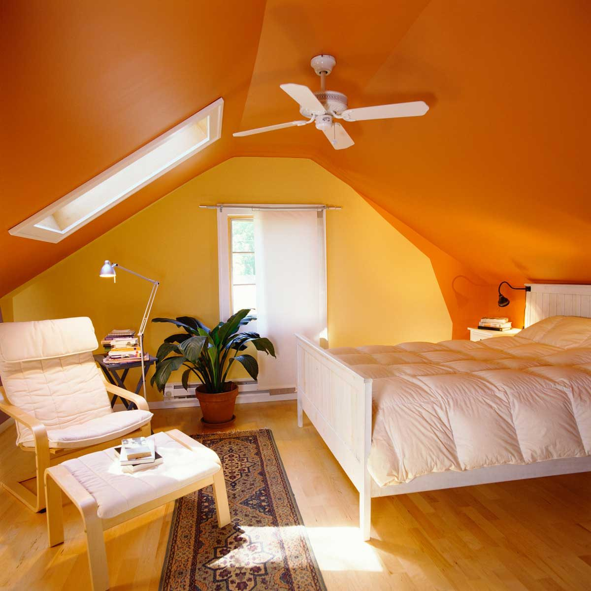 Orange bedroom with a ceiling fan
