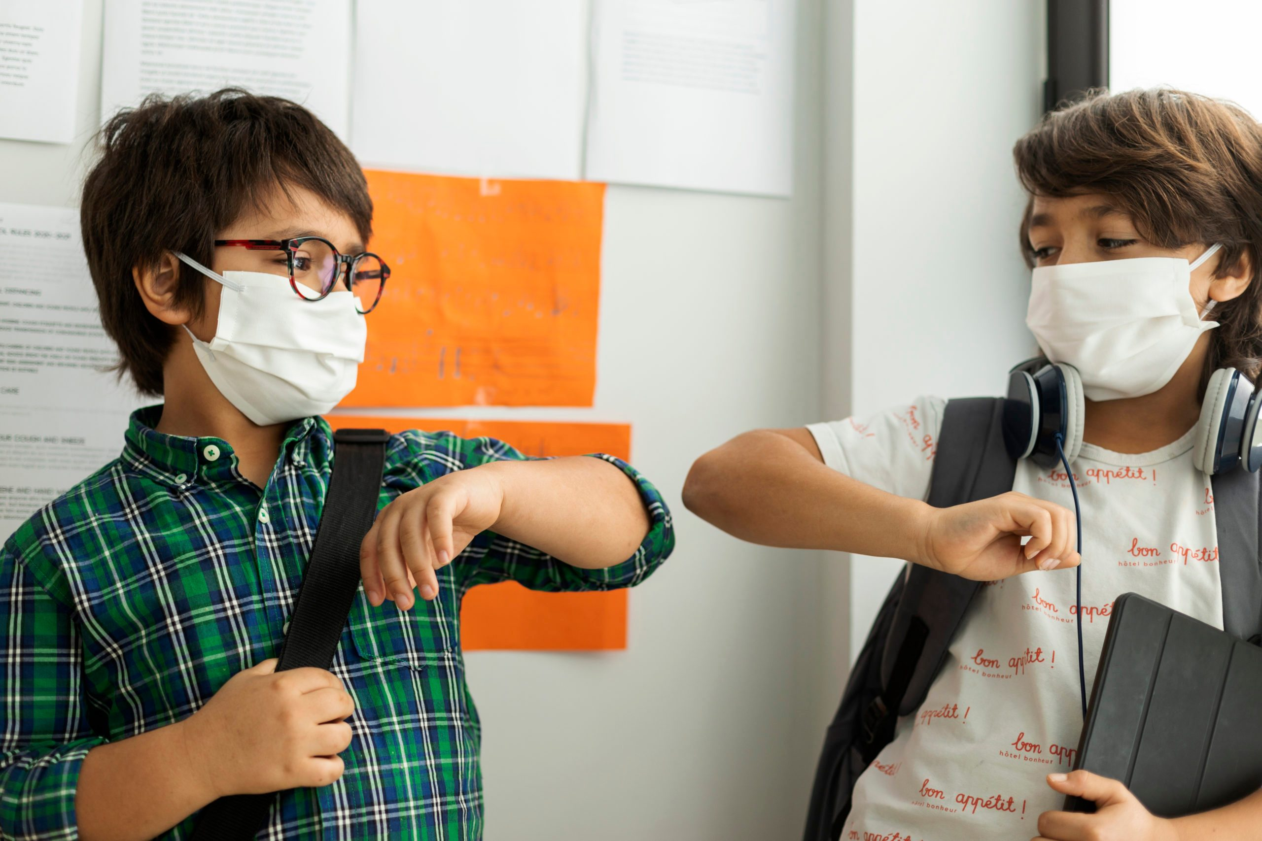 Boys wearing masks giving elbow bump while standing against wall in school
