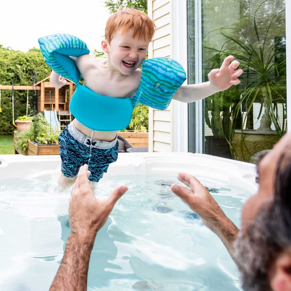 Child jumping into a hot tub