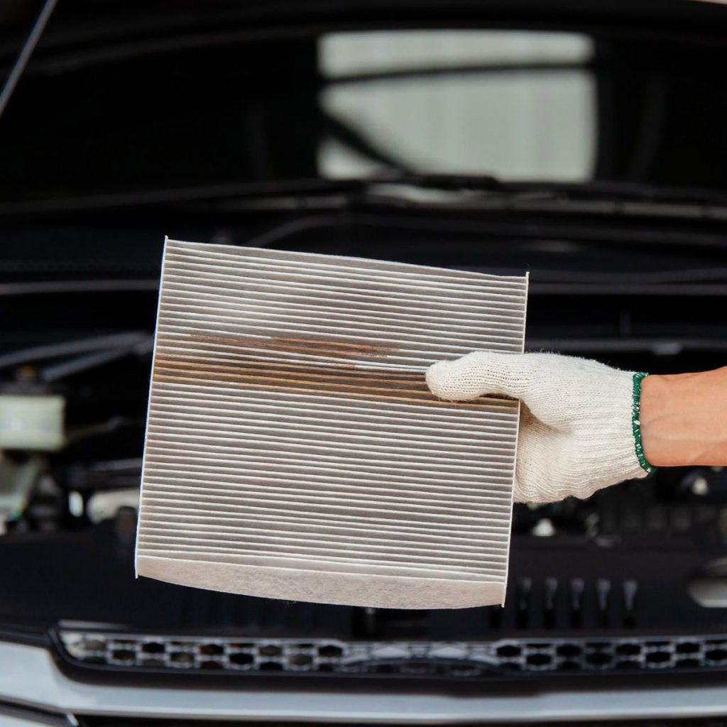 close up of Auto mechanic hands checking an air filter in garage.