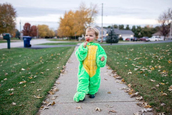 Toddler girl dressed as an alligator eating a sucker on Halloween
