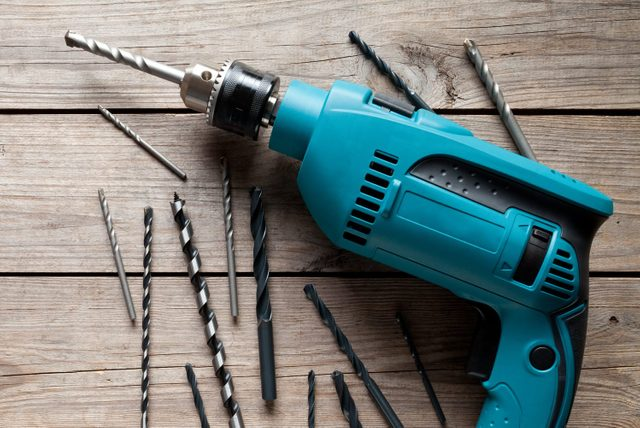 Electric drill on old wooden table