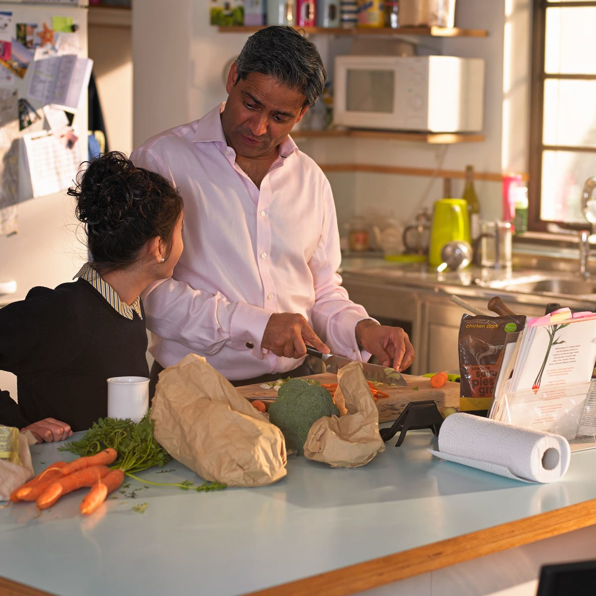 Family preparing a meal from a recipe on an iPad paper towel veggies