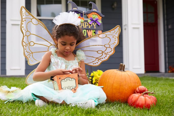 Girl Dressed In Trick Or Treating Fairy Costume On Lawn