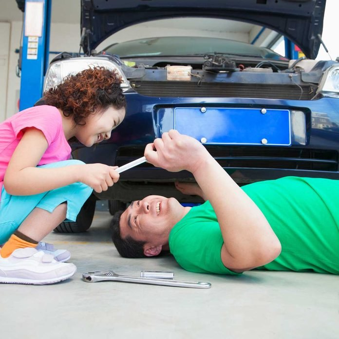 Little girl helping her father change oil