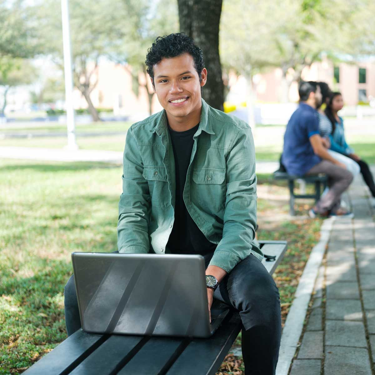 College student sitting outside with a laptop
