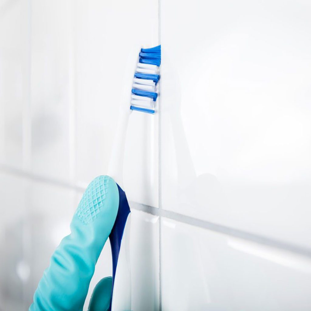 Close-up Of Person Hand Cleaning The Dirty White Tile Of The Wall Using Brush clean grout