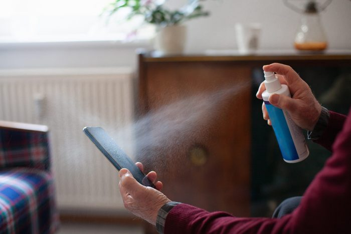 Senior man obsessively cleaning his mobile phone with disinfectant spray, close-up of hands