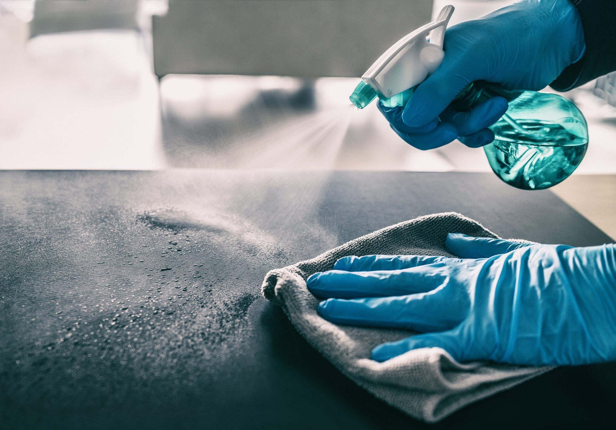 Surface sanitizing against COVID-19 outbreak. Home cleaning spraying antibacterial spray bottle disinfecting against coronavirus wearing nitrile gloves. Sanitize hospital surfaces prevention
