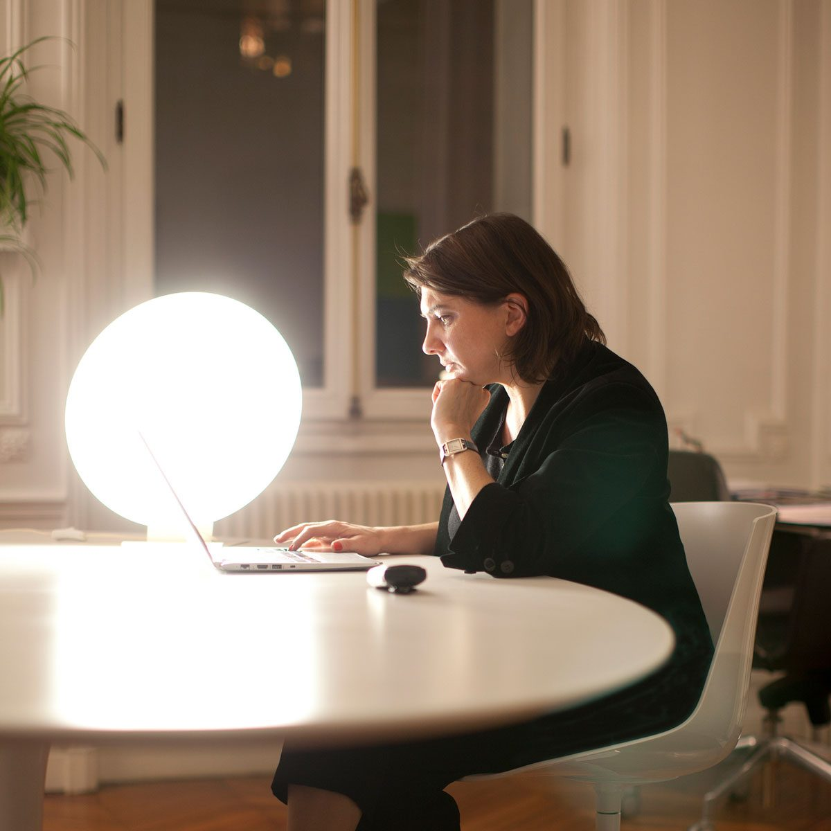 Woman sitting at a table with a light therapy lamp