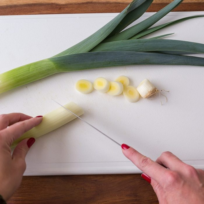 Hands of person slicing leeks on white cutting board, healthy eating concept