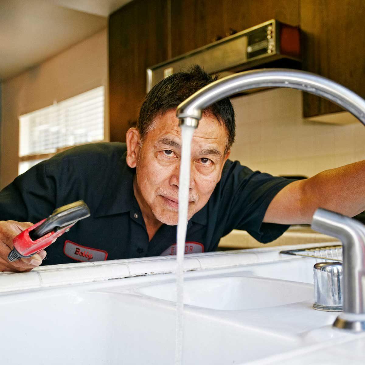 Pro plumber fixing sink