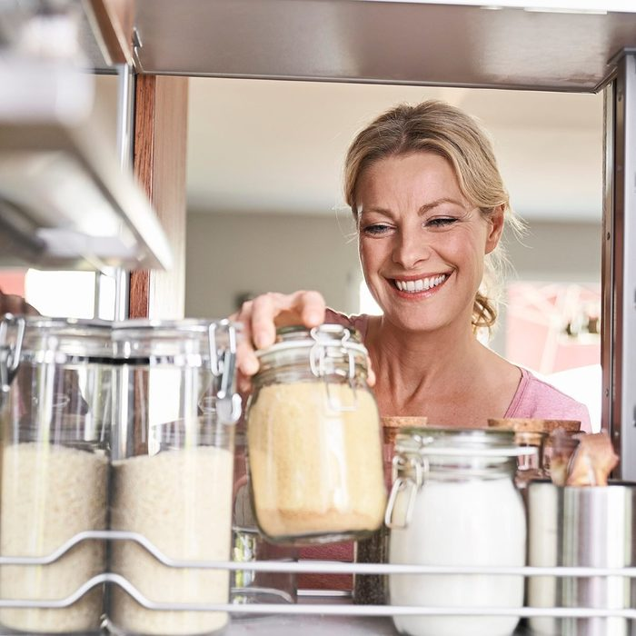 Smiling woman in kitchen taking jar from kitchen cabinet