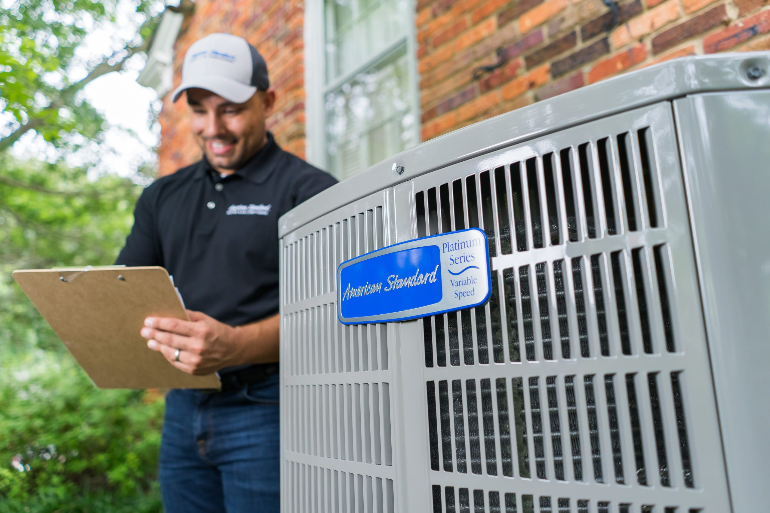 Close up on logo of Platinum 20 Heat Pump / Air Conditioner placed outside while American Standard technician makes notes