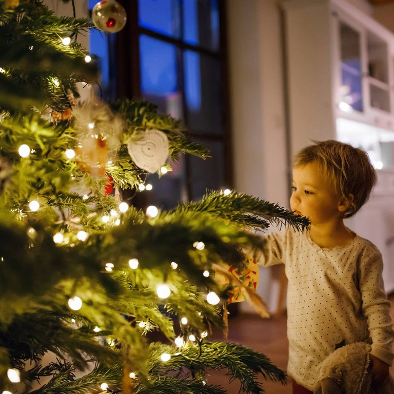 A small toddler girl looking at Christmas tree lights indoors