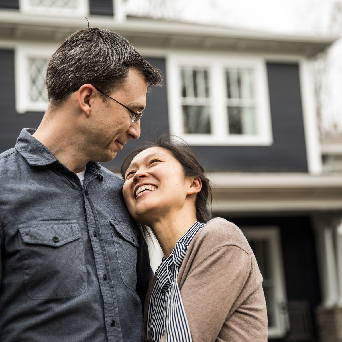 buying a home Couple standing in front of home