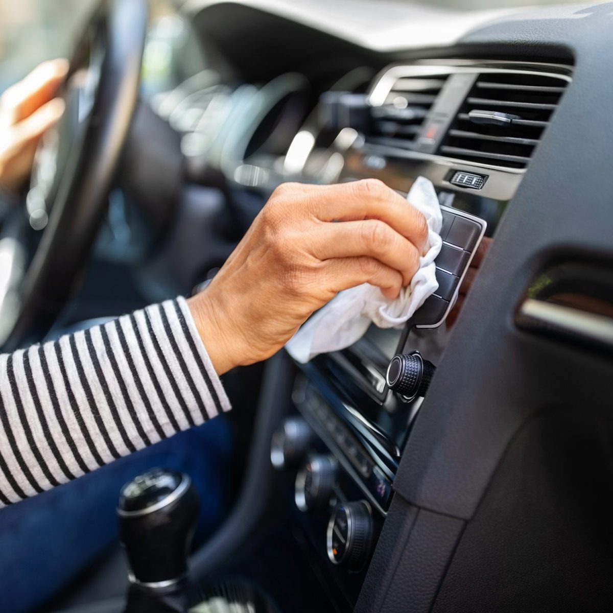 Female hands cleaning car vents with wipe