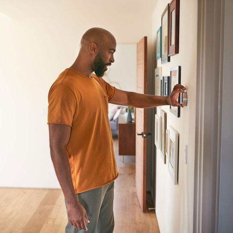 man checking thermostat