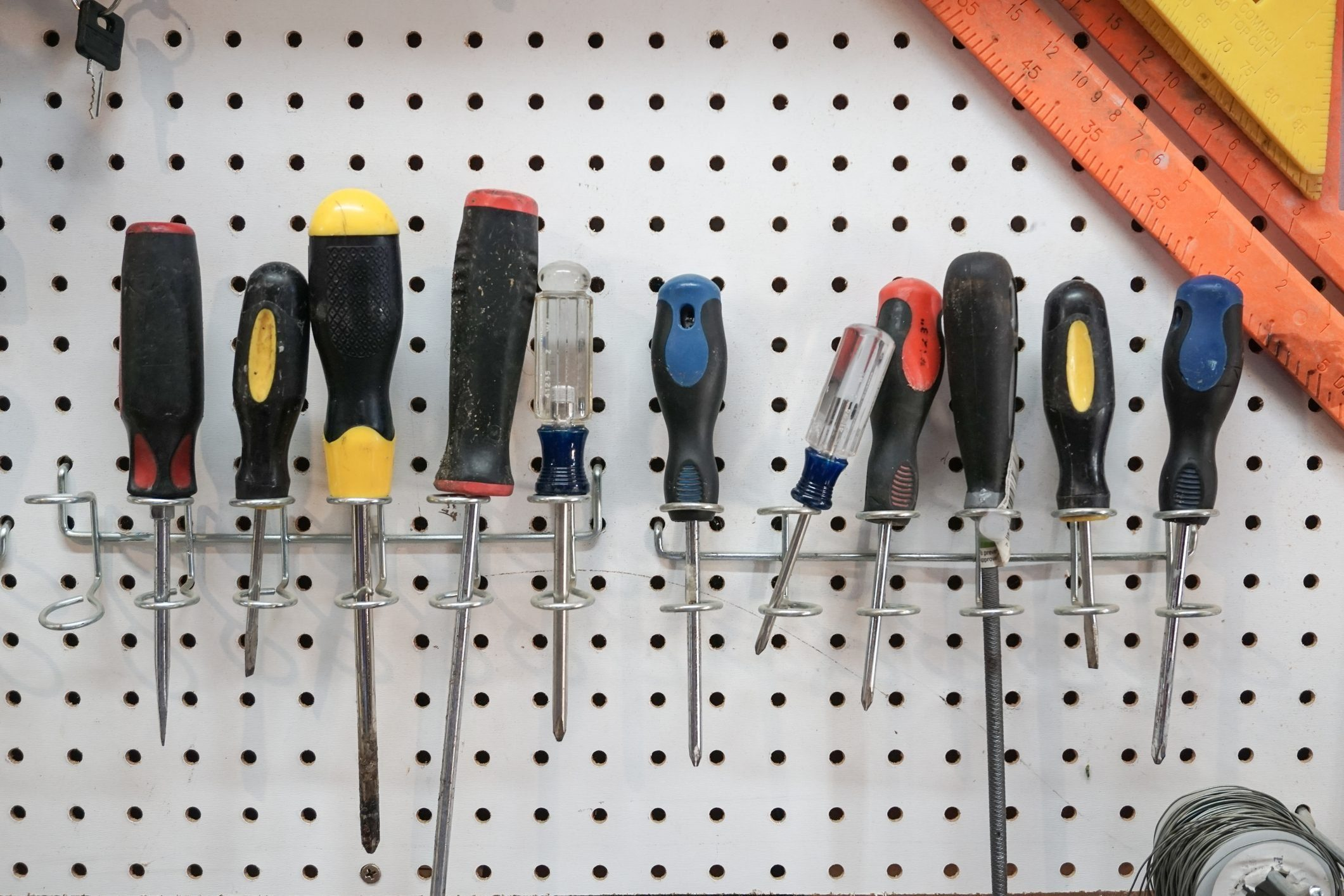 A collection of screwdrivers hanging from a pegboard