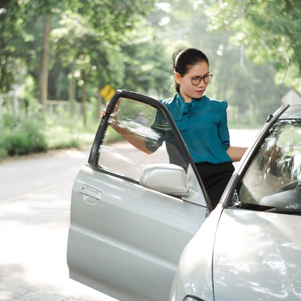 Woman closing a car door