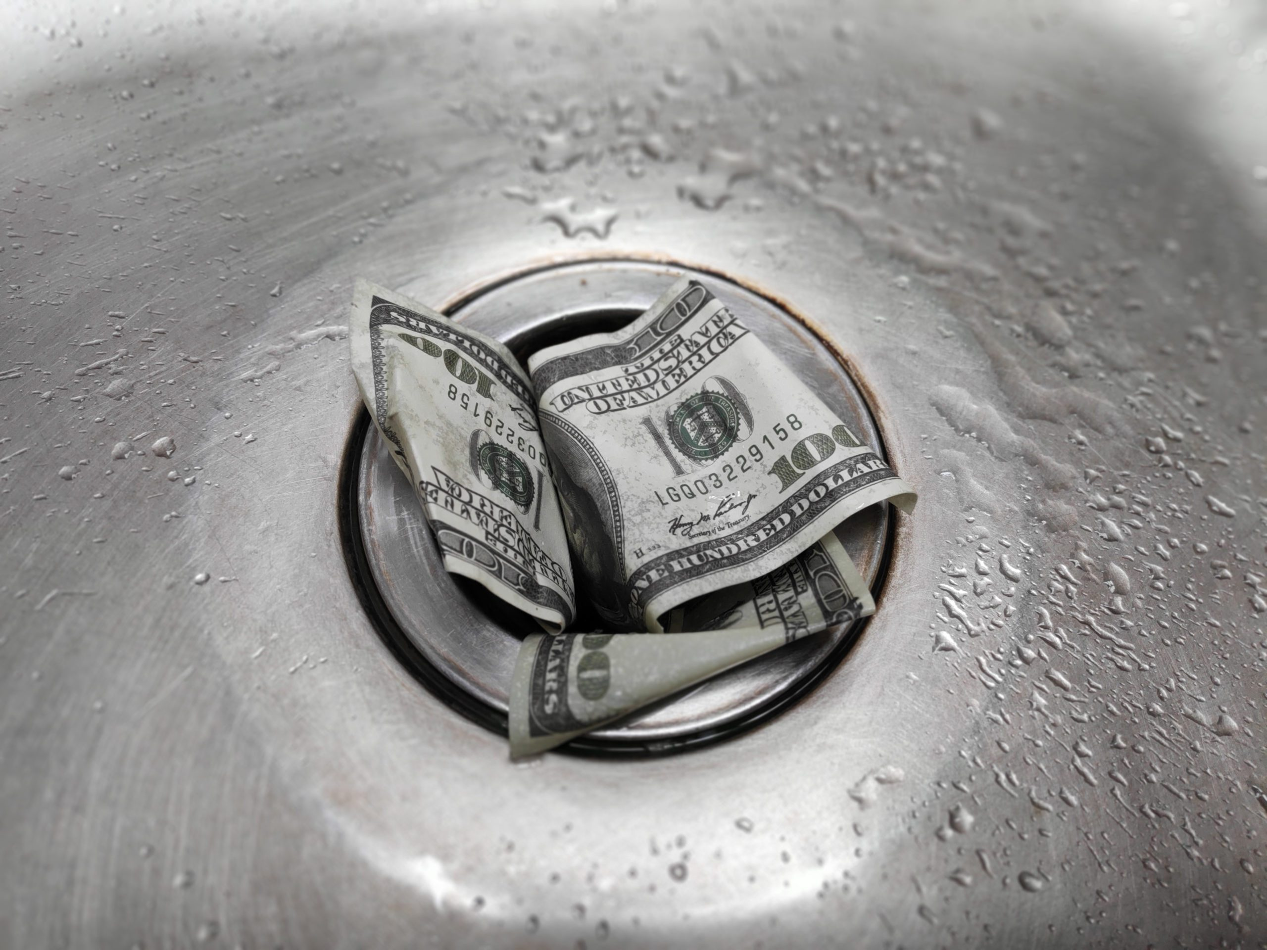 Money is thrown away in the sink. This photo concept illustrates the financial condition of a business that is failing or going bankrupt so that it only wastes money without results.