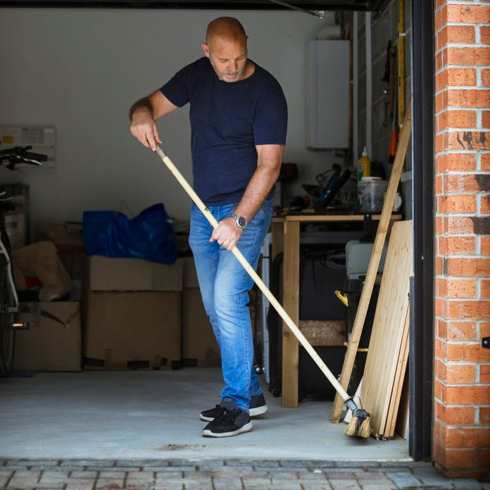 Man sweeping his garage floor