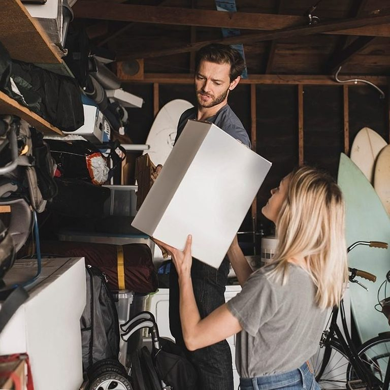Mid Adult Couple Arranging Box In Storage Room