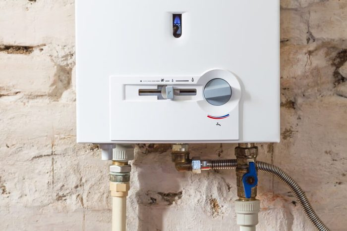 Closeup of gas water heater on a brick wall. Gas boiler in boiler room for hot water