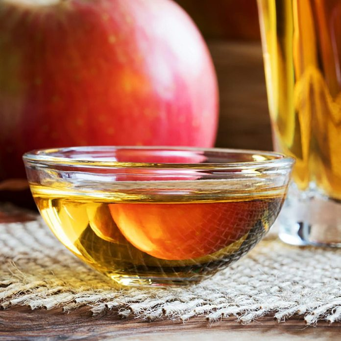 Apple-cider-vinegar in a bowl with glass of vinegar and an apple in the background