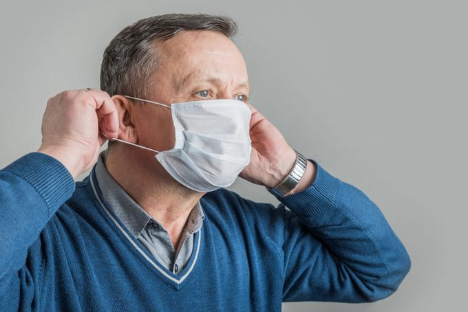 Adult man puts on surgical mask to protect against virus Covid 19. Prevention of Coronavirus.