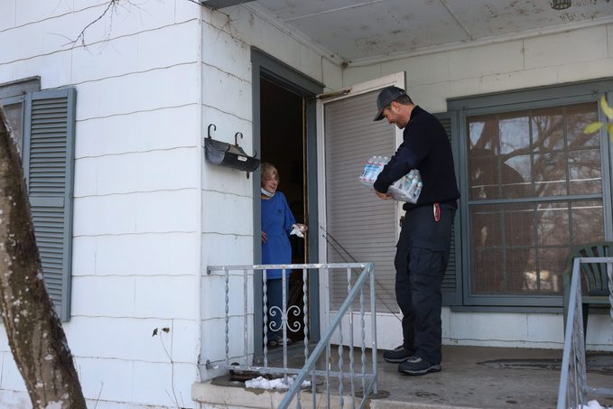 Jason Parish, a volunteer with the Austin Disaster Relief Network, delivers water to Beth Placek on February 19, 2021 in Austin, Texas.