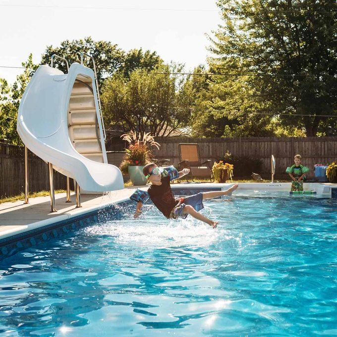 Boy looking at brother jumping in swimming pool on sunny day water slide Gettyimages 961076954 Slide