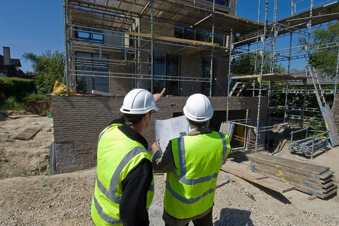 Architects Surveying Plans As They Build A House
