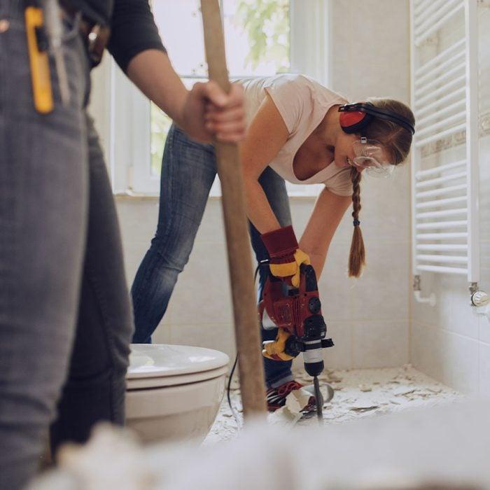 Woman refurbishing bathroom.