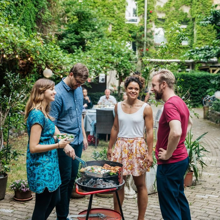 Group Of Friends Cooking On BBQ In Courtyard