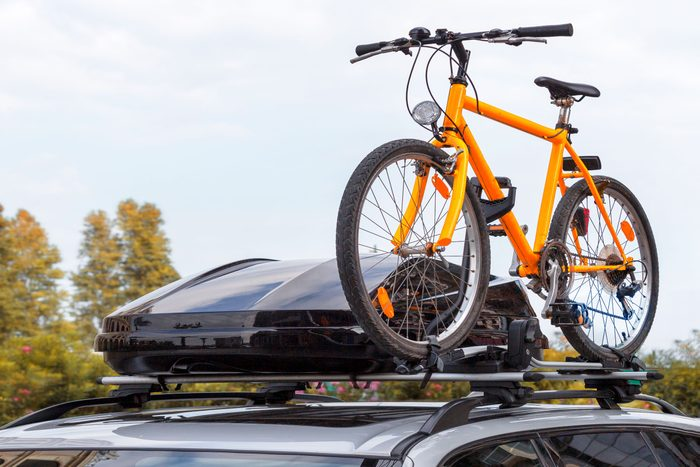 cargo box and orange bicycle attached to a roof rack on a car