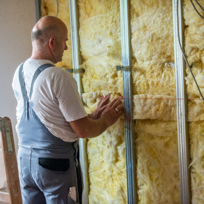 Man working on rock wool of an home wall