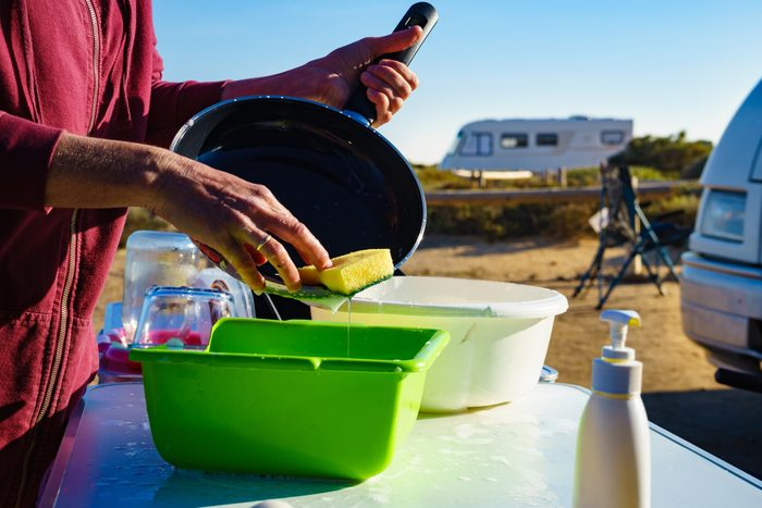 Woman washing dishes in a bin while camping
