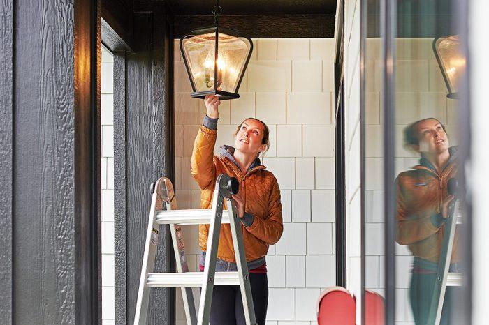woman fixing outdoor light fixture of house