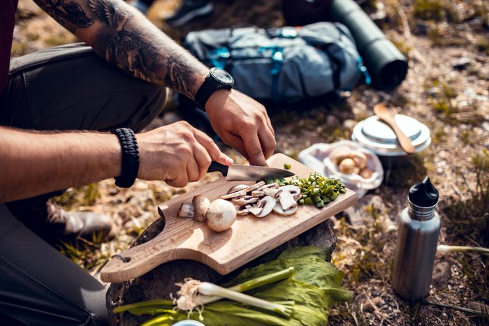 Chopping fresh vegetables for campfire cooking