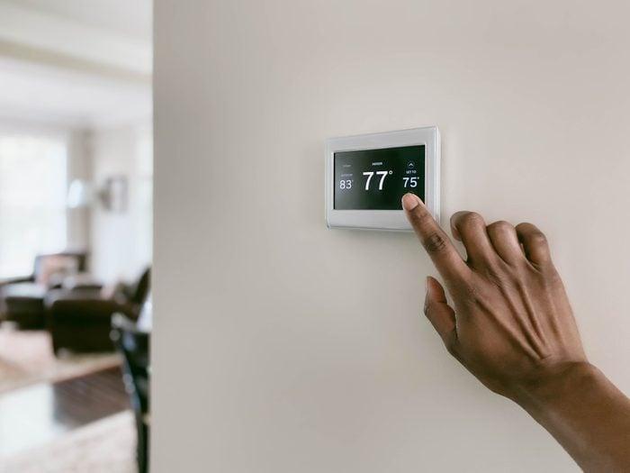 Woman Adjusts Thermostat