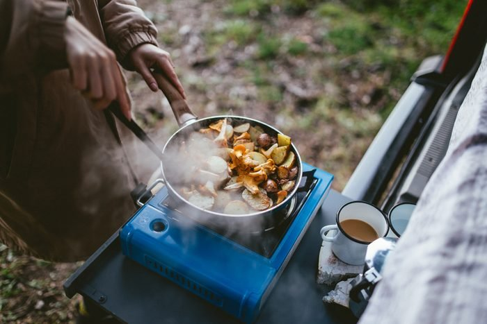 person cooking food with portable camping stove in nature