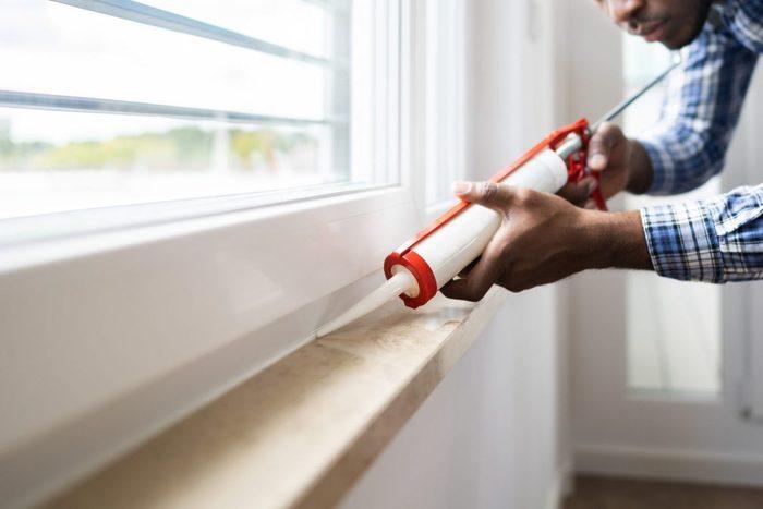 man applying caulk sealant to window frame in house