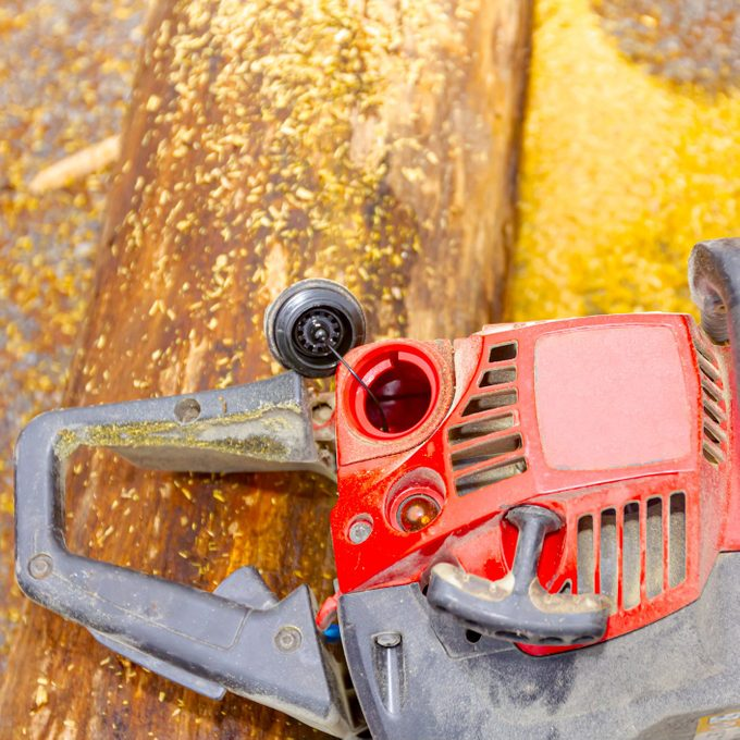 Chainsaw putted down on the stumps with open fuel reservoir