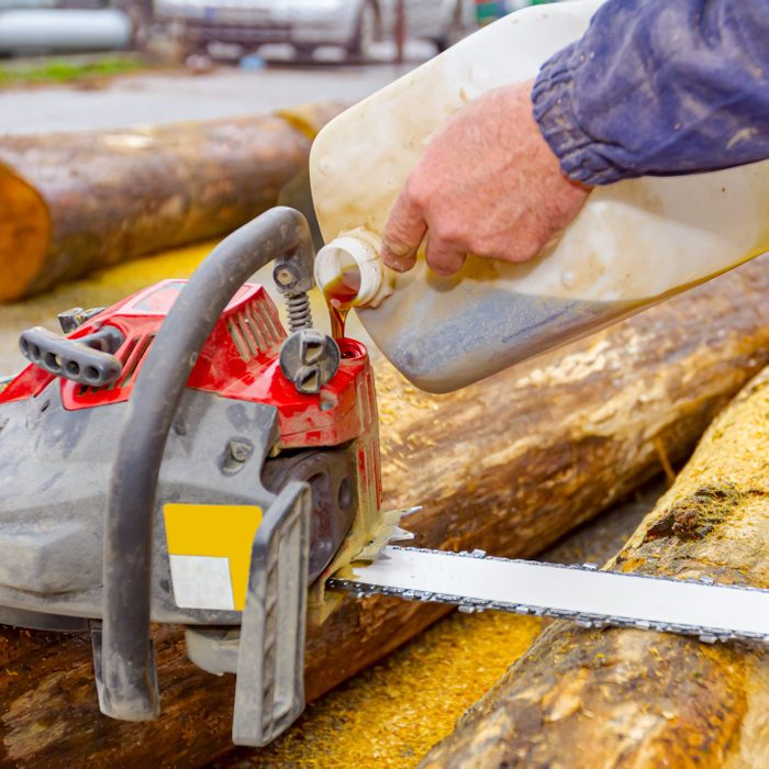 Carpenter pours motor oil from a plastic bottle into a chainsaw