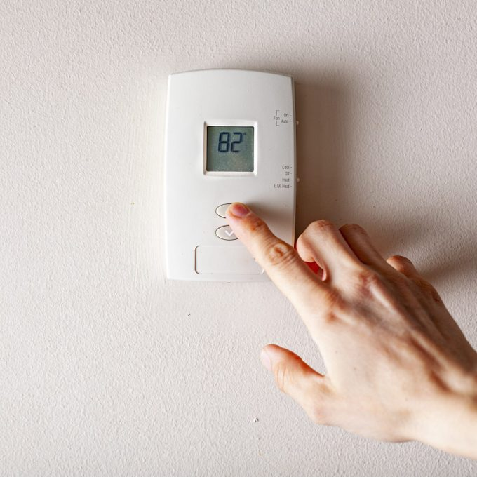 A woman is pressing the up button of a wall attached house thermostat with digital display showing the temperature